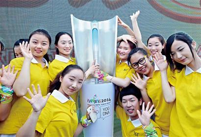 南京/■3月22日,参加发布活动的南京青年学生在南京青奥会火炬旁...
